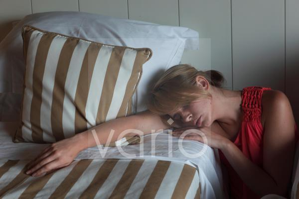 Young woman napping at the edge of bed