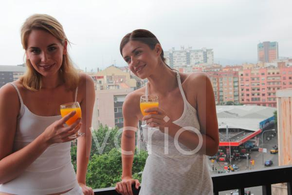 A smiling lesbian couple having orange juice at balcony