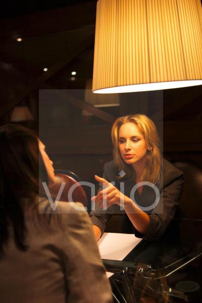 Two business women in conversation sitting under illuminated lamp