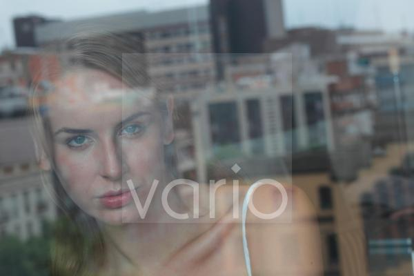 Reflection of beautiful young woman on window