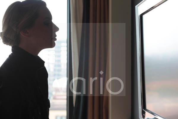 Side view of young woman looking at flat screen television