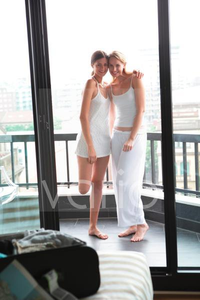 Portrait of cheerful lesbian couple standing in balcony with arm around