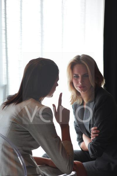Two young business women in conversation
