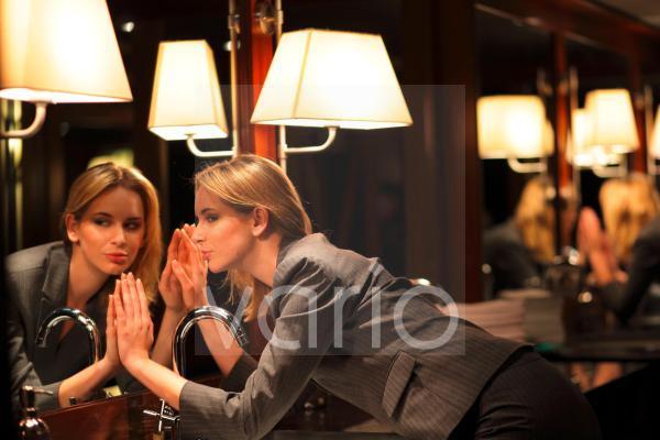 Businesswoman touching bathroom mirror
