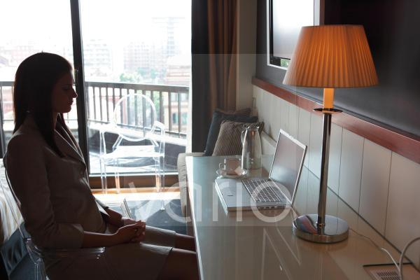 Side view of businesswoman sitting by illuminated lamp
