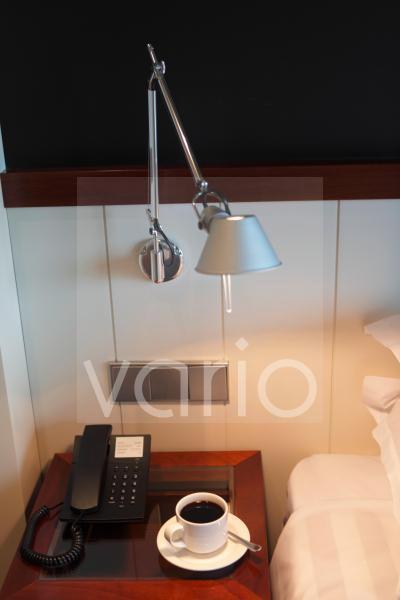 Black tea with landline phone kept on table under illuminated lamp