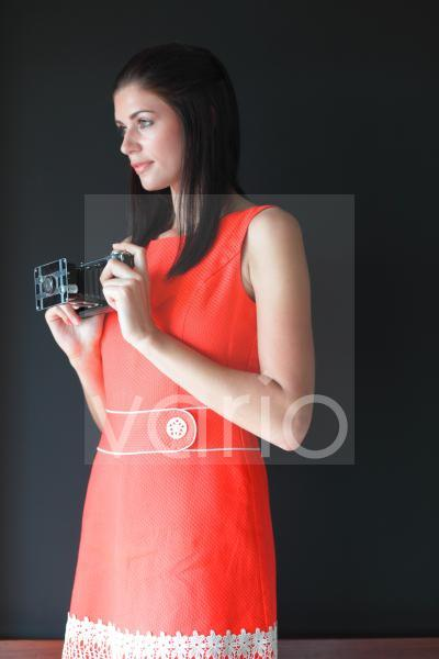 Side view of beautiful young woman holding camera