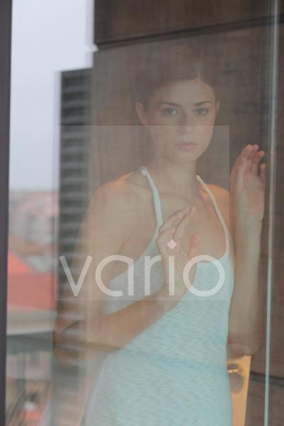 Portrait of young woman contemplating, looking through window