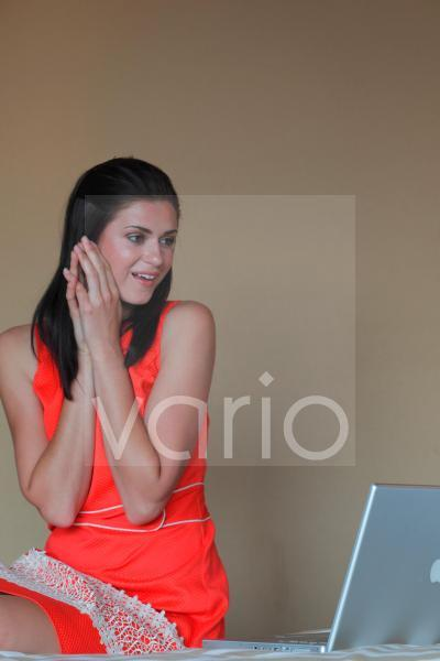 Smiling young woman sitting by laptop with hands clasped