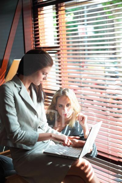 Young businesswoman using laptop while other woman sitting behind her by blinds