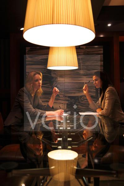 Two young business women holding pens sitting under illuminated lamp