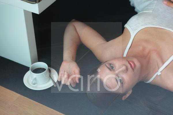 Portrait of cheerless young woman lying on floor