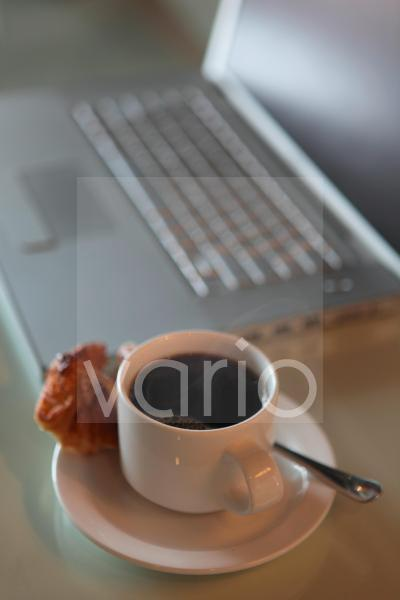 Close-up of tea cup by laptop on table