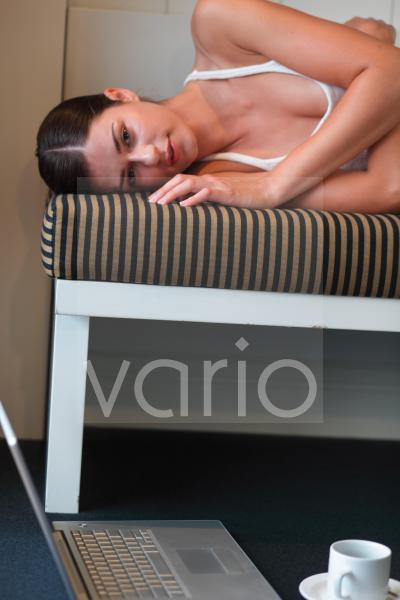 Cheerless young woman relaxing on mattress