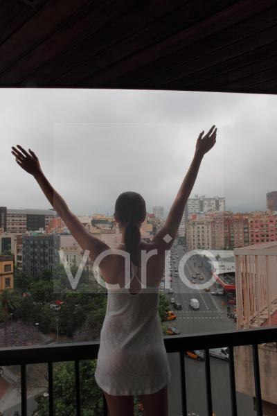 Rear view of woman watching from balcony with arms outstretched
