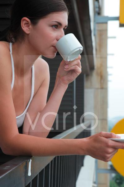Beautiful young woman drinking tea in hotel balcony