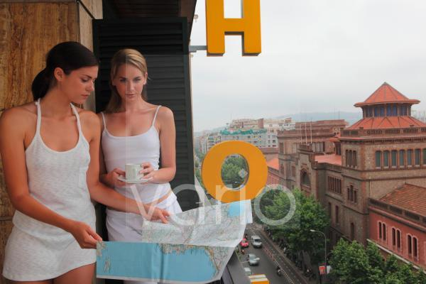 Two gorgeous young women standing in hotel balcony looking at map, one woman holding teacup