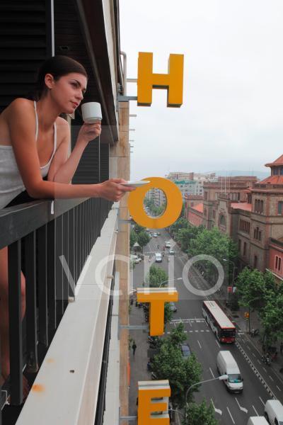 Beautiful young woman drinking morning tea on balcony