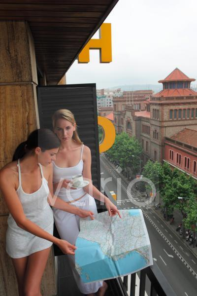 Two sexy young women looking at map in balcony