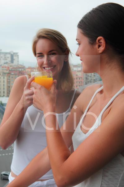A lesbian couple toasting glasses of orange juice