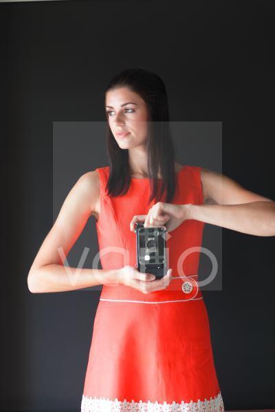 Beautiful young woman holding camera, looking away