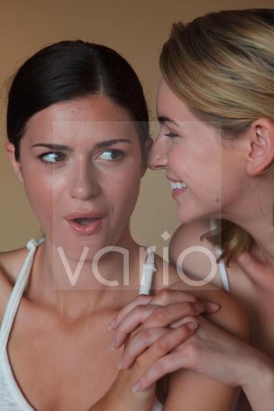 Close-up of a lesbian couple holding hands, one whispering in other's ear