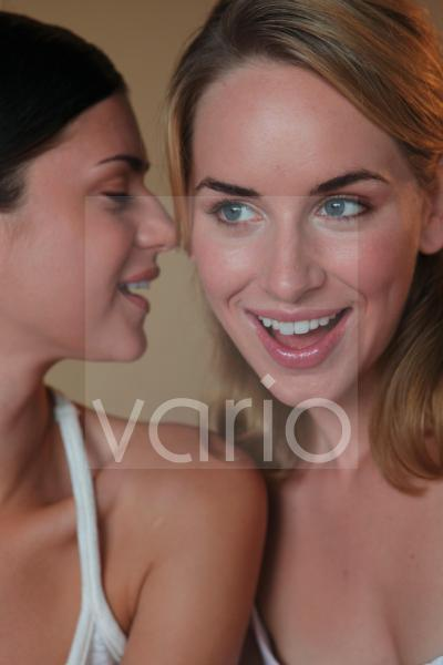 Close-up of a happy lesbian couple, one whispering in other's ear