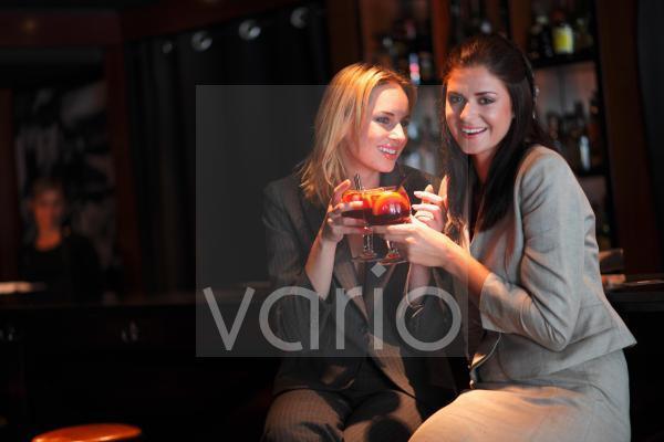 Cheerful lesbian couple toasting drinks