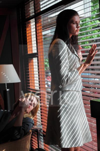 Two young women contemplating, one woman looking through blinds