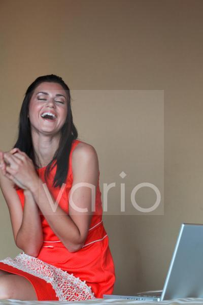 Cheerful young woman sitting by laptop with hands clasped