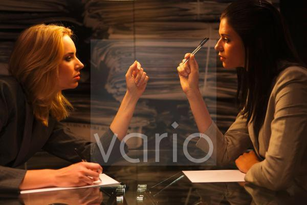 Lesbian businesswomen looking at each other while working at office