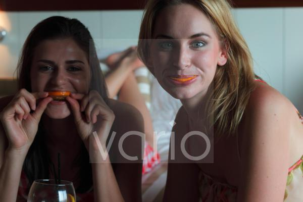 Portrait of a happy lesbian couple holding food in mouth
