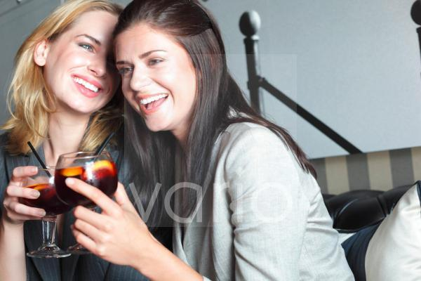 Cheerful lesbian couple holding drinks