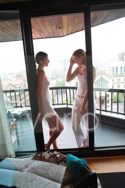 A happy lesbian couple standing at balcony