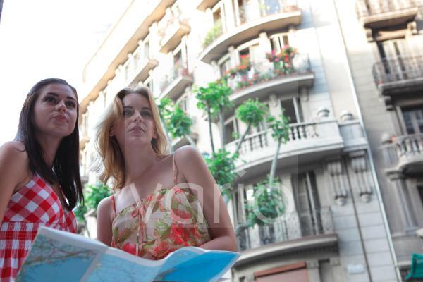 Low angle view of a lesbian couple holding map by building