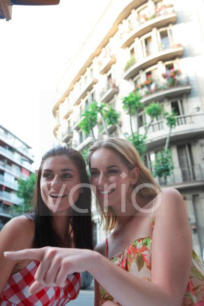 Low angle view of a cheerful lesbian couple enjoying in front of a building