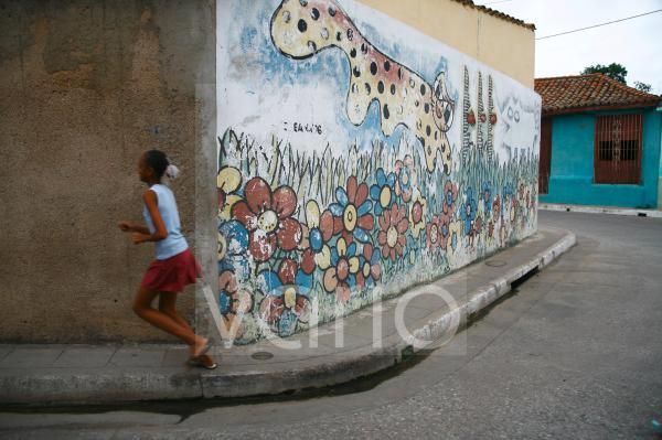 Laufendes Mädchen vor bemalter Wand, Camagüey, Kuba, Große Antillen, Karibik