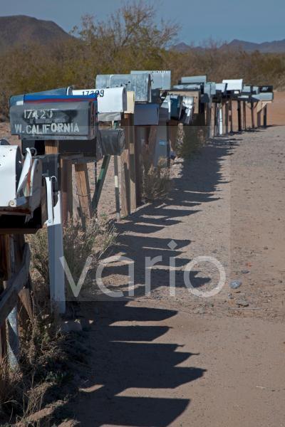 Eine lange Reihe mit Briefkästen stehen entland einer unbefestigten Straße in der Wüste westlich von Tuscon, Three Points, Arizona, USA