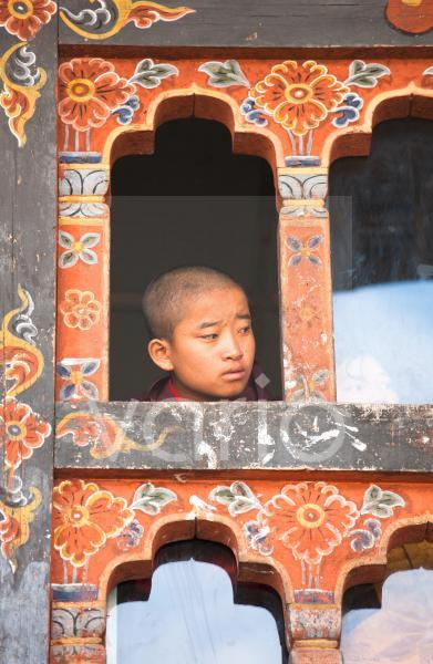Young boy looking out of window above the main courtyard of the Wangdue Phodrang Dzong during Wangdue Phodrang Tsechu, Wangdue Phodrang (Wangdi), Bhutan, Asia