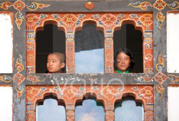 Girl and boy looking out of windows in room above the main courtyard of Wangdue Phodrang Dzong during Wangdue Phodrang Tsechu, Wangdue Phodrang (Wangdi), Bhutan, Asia