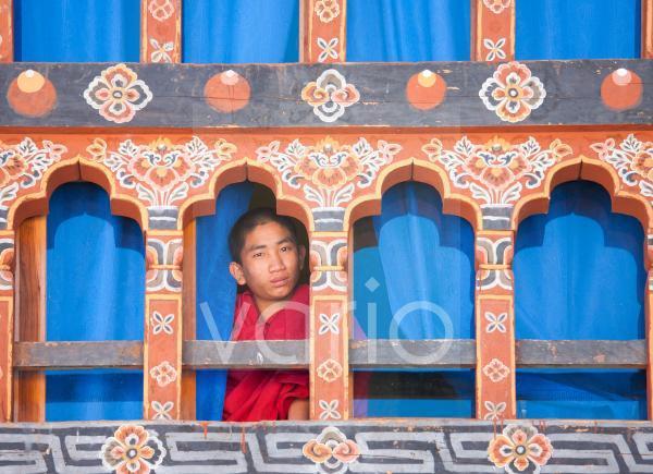 Young Buddhist monk looking out of a window at Trongsa Dzong, Trongsa, Bhutan, Asia