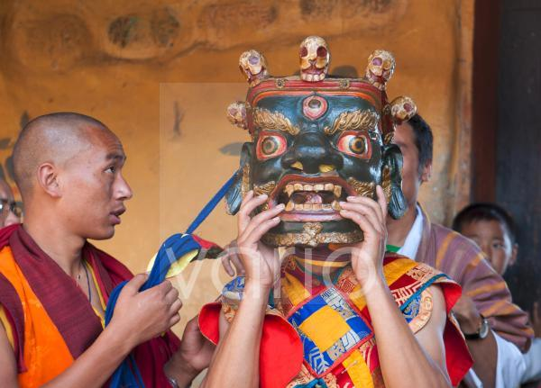 Buddhist monk being helped to secure his carved wooden mask in readiness to take part in traditional dance at the Tamshing Phala Choepa Tsechu, near Jakar, Bumthang, Bhutan, Asia
