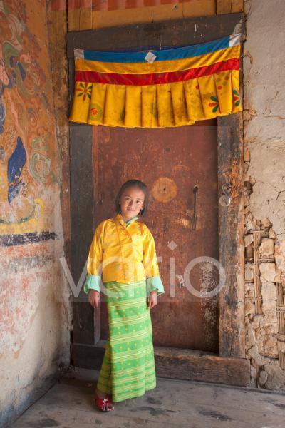 Young girl in national dress standing in doorway beneath colourful Buddhist banner at the Tamshing Phala Choepa Tsechu, near Jakar, Bumthang, Bhutan, Asia