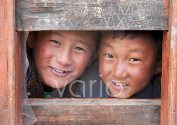 Two young boys looking through a window at their school in Ura Village, Ura Valley, Bumthang, Bhutan, Asia
