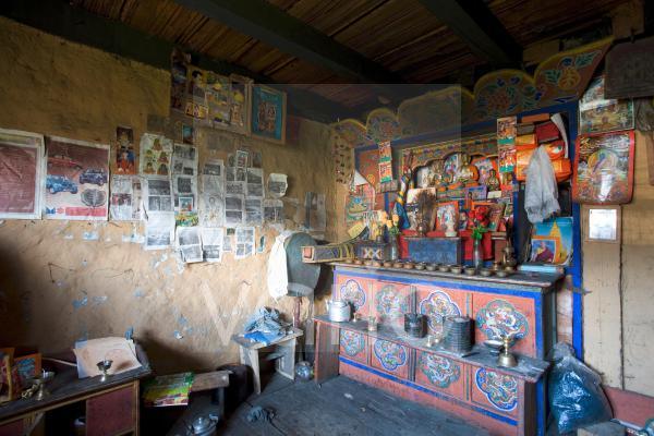 Dimly lit interior of a traditional rural Bhutanese house, Ura village, near Jakar, Bumthang, Bhutan, Asia