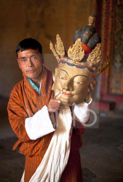 Local man holding an old golden mask with cracks visible in the face, Gangtey Tsechu at Gangte Goemba, Gangte, Phobjikha Valley, Bhutan, Asia