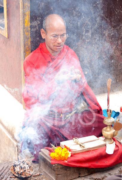 Buddhist monk near Swayambhunath offering to bless people at a roadside altar, Kathmandu, Nepal, Asia
