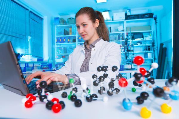 Female chemist using laptop in lab