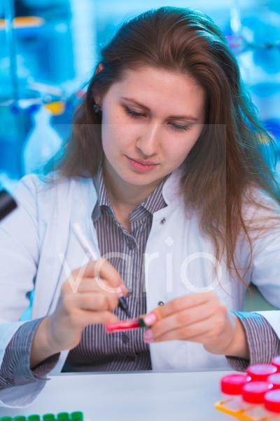 Lab technician writing on a sample
