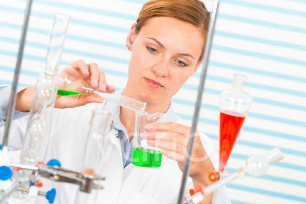 Female chemist pouring chemicals